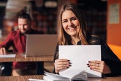 Επιχειρηματίας με τα έγγραφα στα χέρια της που χαμογελά στη κάμερα Στοκ Φωτογραφίες