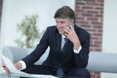Επιχειρηματίας με τα έγγραφα σχετικά με ένα μουτζουρωμένο υπόβαθρο γραφείων Στοκ Φωτογραφίες