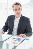 Επιχειρηματίας με τα έγγραφα lap-top και γραφικών παραστάσεων στο γραφείο γραφείων Στοκ Εικόνα
