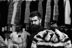 Επιχειρηματίας με τα ακριβά παλτά Το άτομο με το σοβαρό πρόσωπο κρατά τα γούνινα παλτά με το ράφι ενδυμάτων στο υπόβαθρο Μόδα Στοκ Εικόνες