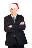 Επιχειρηματίας με τα διπλωμένα όπλα που φορούν το καπέλο santa Στοκ Εικόνα