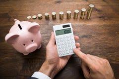 Επιχειρηματίας με τα νομίσματα και Piggybank χρησιμοποιώντας τον υπολογιστή Στοκ Φωτογραφίες