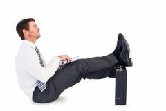 Επιχειρηματίας με τα πόδια επάνω στο χαρτοφύλακα Στοκ Εικόνα