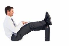 Επιχειρηματίας με τα πόδια επάνω στο χαρτοφύλακα Στοκ Φωτογραφία
