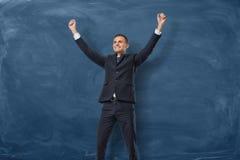 Επιχειρηματίας με τα χέρια που αυξάνονται στη νίκη στο σκούρο μπλε υπόβαθρο πινάκων Στοκ Εικόνες