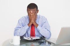 Επιχειρηματίας με τα χέρια που καλύπτουν το πρόσωπο στο γραφείο Στοκ Εικόνες