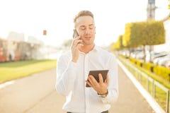 Επιχειρηματίας με την κινητή τηλεφωνική ταμπλέτα στα χέρια Στοκ Εικόνες