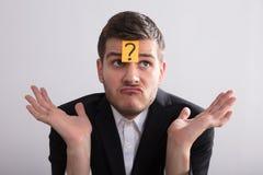 Επιχειρηματίας με την κολλώδη σημείωση ερωτηματικών για το μέτωπό του στοκ εικόνα με δικαίωμα ελεύθερης χρήσης