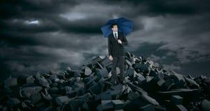 Επιχειρηματίας με την ομπρέλα που στέκεται στους βράχους συντριμμιών κατά τη διάρκεια της θύελλας απόθεμα βίντεο