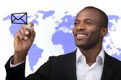 Επιχειρηματίας με την παράδοση παγκόσμιου ταχυδρομείου στο υπόβαθρο παγκόσμιων χαρτών Στοκ Φωτογραφία