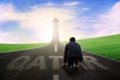 Επιχειρηματίας με τη λέξη και το βέλος του Κατάρ πρός τα πάνω Στοκ φωτογραφία με δικαίωμα ελεύθερης χρήσης