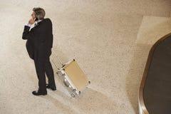 Επιχειρηματίας με τη βαλίτσα από το ιπποδρόμιο αποσκευών στον αερολιμένα Στοκ Εικόνες