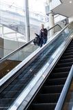 Επιχειρηματίας με τη μεγάλη μαύρη τσάντα και το κινητό τηλέφωνο που κατεβαίνουν στην κυλιόμενη σκάλα Στοκ Εικόνες