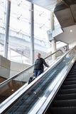 Επιχειρηματίας με τη μεγάλη μαύρη τσάντα και το κινητό τηλέφωνο που κατεβαίνουν στην κυλιόμενη σκάλα Στοκ Φωτογραφίες