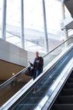 Επιχειρηματίας με τη μεγάλη μαύρη τσάντα και το κινητό τηλέφωνο που κατεβαίνουν στην κυλιόμενη σκάλα Στοκ Εικόνα