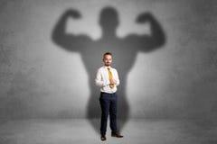 Επιχειρηματίας με τη μυϊκή σκιά πίσω από την πλάτη του Στοκ Εικόνες