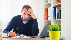 Επιχειρηματίας με τη συνεδρίαση πονοκέφαλου στο γραφείο του. Στοκ φωτογραφία με δικαίωμα ελεύθερης χρήσης