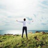 Επιχειρηματίας με τις ανοικτές αγκάλες στον ουρανό έννοια της επιτυχίας και της ελευθερίας Στοκ Φωτογραφία