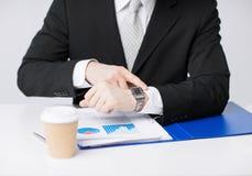 Επιχειρηματίας με τις γραφικές παραστάσεις που δείχνει στο ρολόι Στοκ φωτογραφία με δικαίωμα ελεύθερης χρήσης