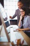 Επιχειρηματίας με τον άνδρα συνάδελφος στο γραφείο υπολογιστών Στοκ Εικόνες