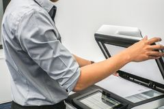 Επιχειρηματίας με τον γκρίζο εκτυπωτή χρήσης πουκάμισων για να ανιχνεύσει τα εμπιστευτικά έγγραφα στην αρχή Στοκ Εικόνες