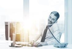 Επιχειρηματίας με τον υπολογιστή που καλεί το τηλέφωνο στο γραφείο Στοκ φωτογραφίες με δικαίωμα ελεύθερης χρήσης