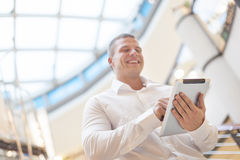 Χαμογελώντας επιχειρηματίας με τον υπολογιστή ταμπλετών στη σύγχρονη επιχείρηση buil Στοκ φωτογραφία με δικαίωμα ελεύθερης χρήσης