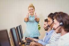 Επιχειρηματίας με τους αντίχειρες που στέκονται επάνω στους υπαλλήλους Στοκ Εικόνες