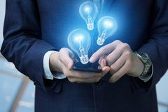 Επιχειρηματίας με τους κινητούς και λαμπτήρες φω'των Στοκ Εικόνες