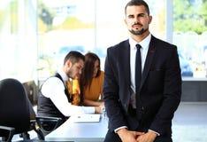 Επιχειρηματίας με τους συναδέλφους στην ανασκόπηση στοκ φωτογραφία με δικαίωμα ελεύθερης χρήσης