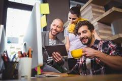 Επιχειρηματίας με τους συναδέλφους στο γραφείο υπολογιστών στην αρχή Στοκ Φωτογραφία