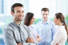 Επιχειρηματίας με τους συναδέλφους στο υπόβαθρο στοκ εικόνες