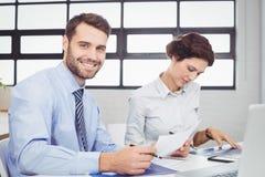 Επιχειρηματίας με το έγγραφο ενώ θηλυκή συνεδρίαση συναδέλφων εκτός από Στοκ εικόνα με δικαίωμα ελεύθερης χρήσης
