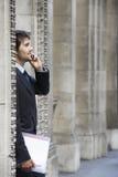 Επιχειρηματίας με το αρχείο που χρησιμοποιεί το κινητό τηλέφωνο Στοκ Εικόνες