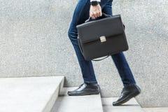 Επιχειρηματίας με το διαθέσιμο περπάτημα χαρτοφυλάκων επάνω στα σκαλοπάτια Στοκ Εικόνες