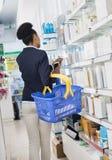 Επιχειρηματίας με το καλάθι και τηλέφωνο που επιλέγει τα προϊόντα σε Pharma στοκ φωτογραφία με δικαίωμα ελεύθερης χρήσης