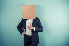 Επιχειρηματίας με το κιβώτιο στον επικεφαλής δίνοντας αντίχειρά του επάνω Στοκ Φωτογραφία