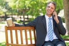 Επιχειρηματίας με το μίας χρήσης φλυτζάνι που απαντά στο κινητό τηλέφωνο Στοκ φωτογραφία με δικαίωμα ελεύθερης χρήσης