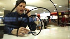 Επιχειρηματίας με το μαξιλάρι στον καφέ που μιλά στο τηλέφωνο απόθεμα βίντεο