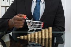 Επιχειρηματίας με το μικρά κάρρο και τα νομίσματα αγορών Στοκ Εικόνες