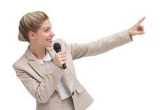 Επιχειρηματίας με το μικρόφωνο που δείχνει κάτι Στοκ εικόνες με δικαίωμα ελεύθερης χρήσης