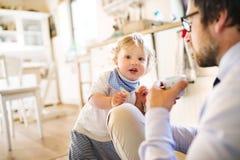 Επιχειρηματίας με το μικρό γιο του στο σπίτι, που πίνει τον καφέ Στοκ Φωτογραφία