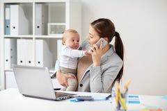 Επιχειρηματίας με το μωρό και smartphone στο γραφείο Στοκ Εικόνες