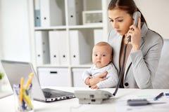 Επιχειρηματίας με το μωρό που καλεί το τηλέφωνο στο γραφείο Στοκ Φωτογραφία