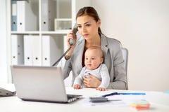 Επιχειρηματίας με το μωρό που καλεί το τηλέφωνο στο γραφείο Στοκ Εικόνες