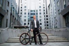 Επιχειρηματίας με το ποδήλατο που ανεβαίνει τα σκαλοπάτια στο υπόβαθρο των εμπορικών κέντρων Στοκ Φωτογραφίες
