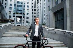 Επιχειρηματίας με το ποδήλατο που ανεβαίνει τα σκαλοπάτια στο υπόβαθρο των εμπορικών κέντρων Στοκ φωτογραφία με δικαίωμα ελεύθερης χρήσης