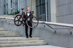 Επιχειρηματίας με το ποδήλατο που ανεβαίνει τα σκαλοπάτια στο υπόβαθρο των εμπορικών κέντρων Στοκ εικόνες με δικαίωμα ελεύθερης χρήσης