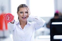 Επιχειρηματίας με το ρολόι που είναι αργά για τα προϊόντα της Στοκ Εικόνα