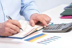 Επιχειρηματίας με το σημειωματάριο στο γραφείο Στοκ εικόνα με δικαίωμα ελεύθερης χρήσης